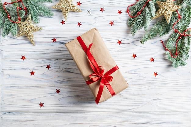 Prezent cristmas zawinięty w papier rzemieślniczy z czerwoną wstążką, gałęzie jodły