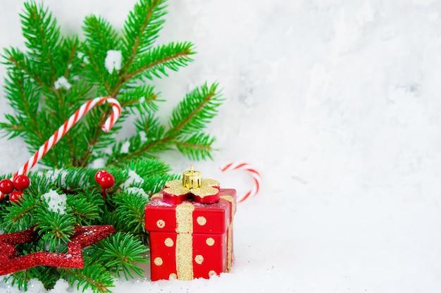 Prezent, dekoracje i gałęzie jodły w śniegu