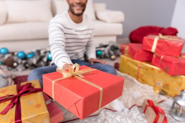 Prezent dla ciebie. selektywne skupienie się na prezentie świątecznym zawiniętym w papier do pakowania i oferowanym tobie, gdy jest trzymany przez pozytywnego, słodkiego młodzieńca