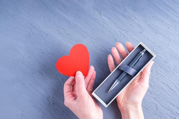 Prezent dla mężczyzny. kobiece ręce trzymają pudełko z długopisem i papierowym sercem