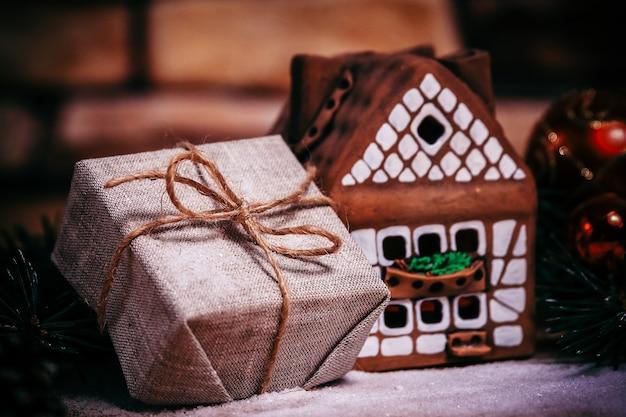 Prezent gwiazdkowy, domek z piernika i ozdoby świąteczne.