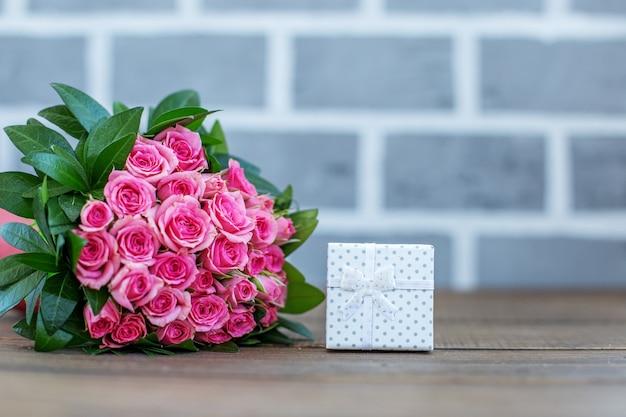 Prezent i bukiet róż. miejsce na napis. koncepcja lo