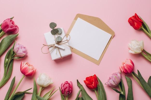 Prezent i karta na różowym tle z tulipanami.
