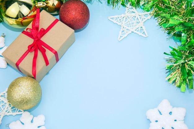 Prezent i ozdoby świąteczne na niebieskim tle. pudełko z czerwoną wstążką.