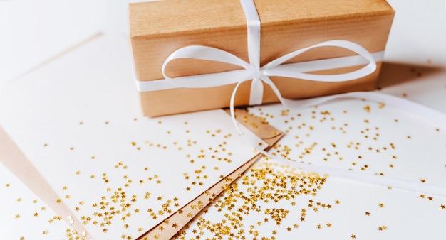 Prezent i pusta notatka z kopertą, złote gwiazdy brokatu na białym tle