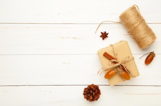 Prezent, jesienne liście, laski cynamonu, gwiazdki anyżu, szyszki