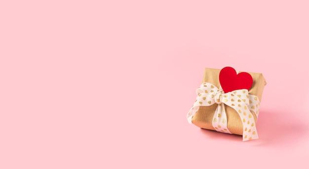 Prezent lub obecne pudełko z czerwonym sercem na różowym tle. pastelowe kolory, miejsce na tekst i projekt
