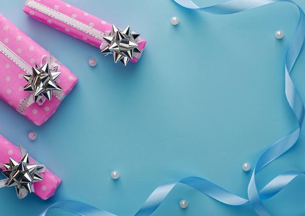 Prezent lub obecne różowe pudełka ze wstążką na niebieskim tle