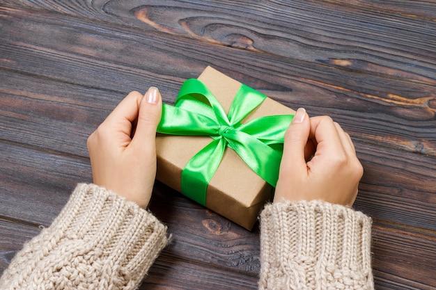 Prezent lub prezent z zieloną kokardą. kobiet ręki pokazuje prezenty i daje.