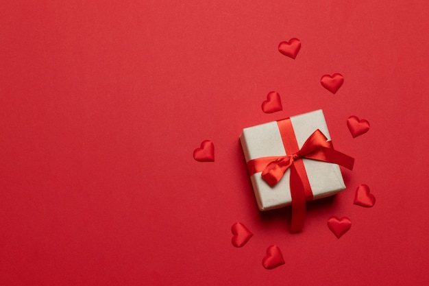 Prezent lub pudełko z czerwoną wstążką i miłosnym kształtem na czerwonym stole. modna kompozycja na urodziny, dzień matki lub ślub.