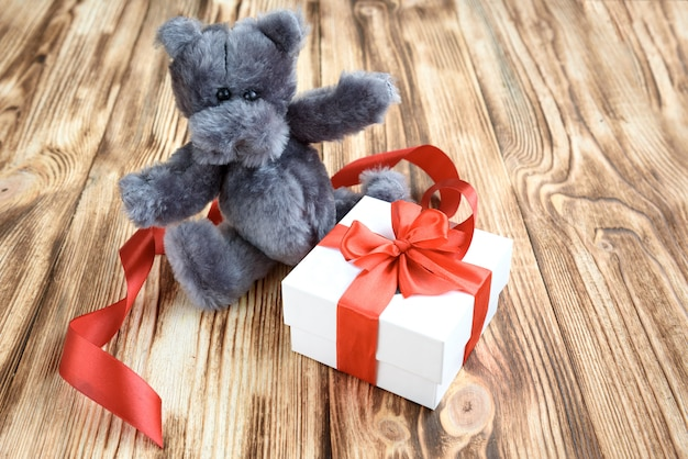 Prezent łuk z czerwoną wstążką łuk i szary niedźwiedź zabawka na drewniane tła.