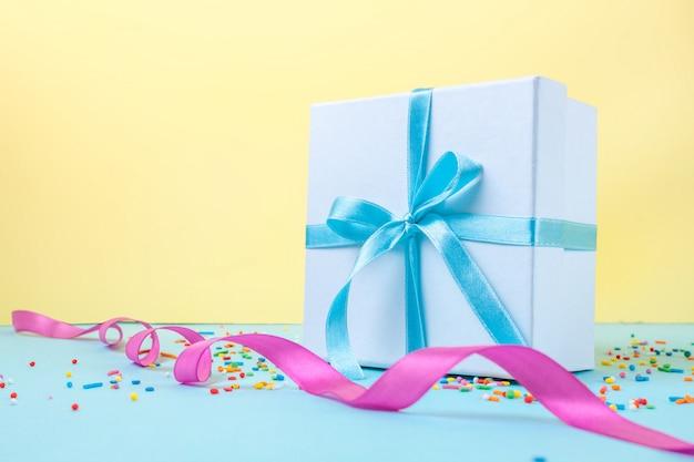 Prezent, małe pudełko przewiązane satynową niebieską wstążką. koncepcja prezent. gratulujemy wakacji, wręczamy prezenty.