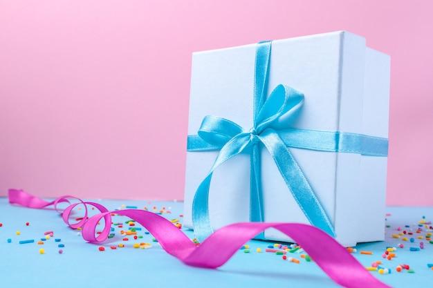 Prezent, małe pudełko przewiązane satynową niebieską wstążką. koncepcja prezent. niespodzianki i prezenty dla bliskich, gratulacje z wakacji, wręczanie prezentów