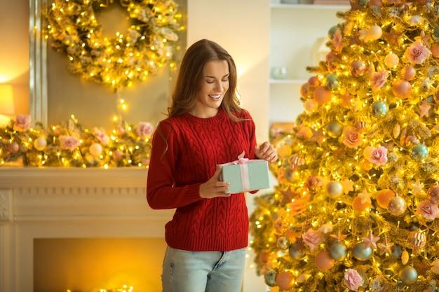 Prezent na boże narodzenie. ciemnowłosa młoda kobieta stojąca z prezentem w dłoniach