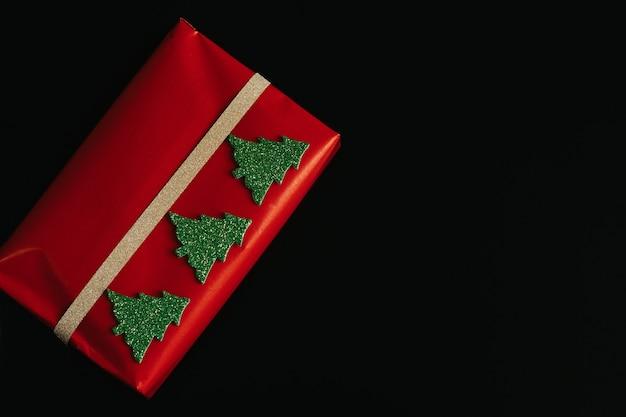 Prezent na boże narodzenie czerwony z czarnym tłem. z kopią miejsca