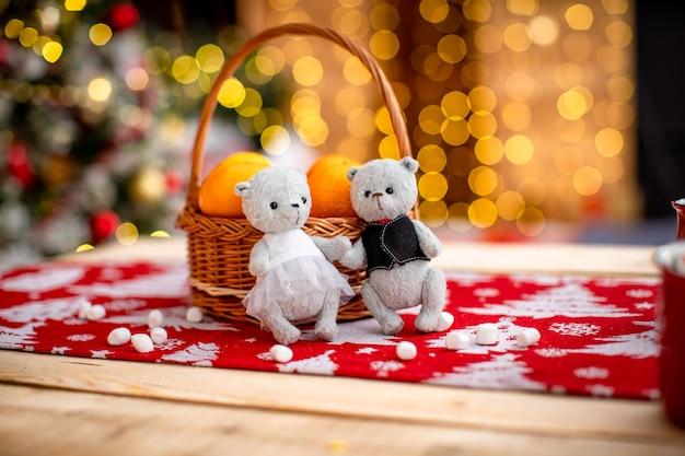 Prezent na boże narodzenie. dwa niedźwiadki chłopiec i dziewczynka ręcznie wykonane z tkaniny. nowy rok przytulne tło. wolne miejsce na tekst