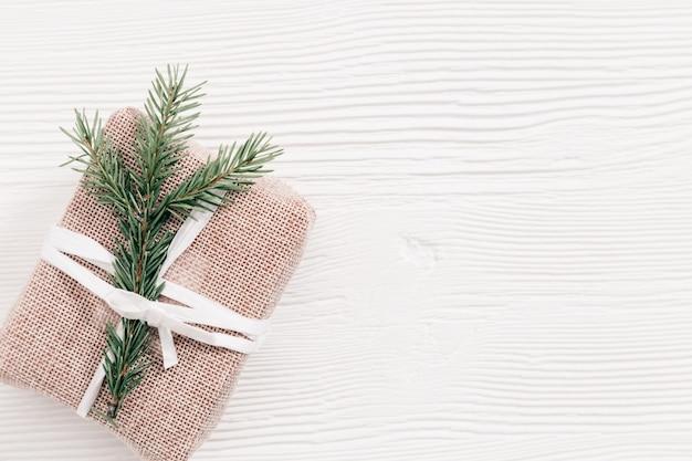 Prezent na boże narodzenie i gałęzie jodły ferie zimowe i nowy rok w tle ręcznie robiony prezent