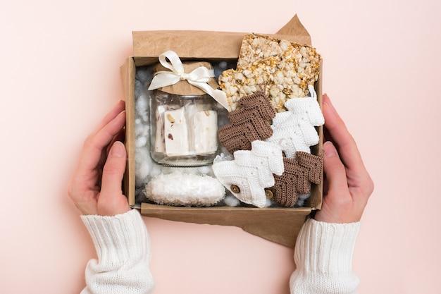 Prezent na boże narodzenie. kobiece dłonie trzymają pudełko ze słoikiem pasty, chipsami zbożowymi i dzianymi jodłami. wystrój rękodzieła. zero marnowania