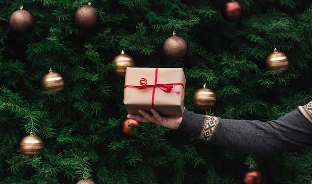 Prezent na boże narodzenie. męska ręka w sweter z dzianiny trzyma pudełko wykonane z papieru rzemieślniczego z czerwoną wstążką na tle choinki