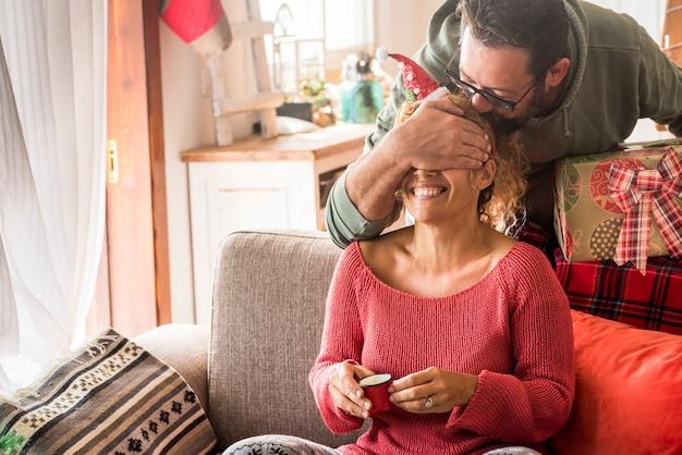 Prezent na boże narodzenie niespodzianka para z mężczyzną robi niespodziankę żonie kobiety w domu