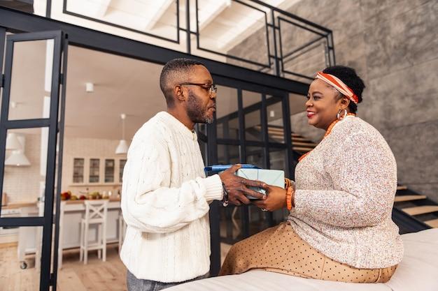 Prezent na boże narodzenie. pozytywny afro american kobieta uśmiecha się podczas odbierania prezentu