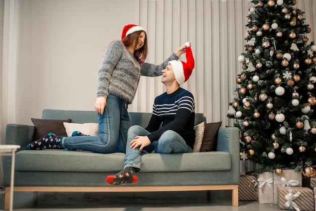 Prezent na boże narodzenie. szczęśliwa para w czapce świętego mikołaja z prezentem na boże narodzenie i nowy rok w domu.