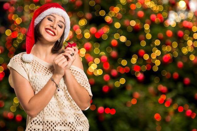 Prezent na boże narodzenie. uśmiechnięta piękna kobieta w czerwonym kapeluszu i szaliku wyobrażając sobie z zamkniętymi oczami, co jest w pudełku, na tle bożego narodzenia