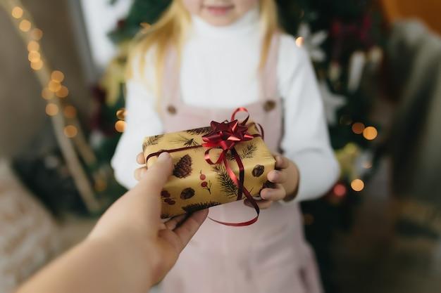 Prezent na boże narodzenie w ręce, dając prezent w domu, mała dziewczynka odbiera prezent gwiazdkowy, dziewczyna trzyma prezent na boże narodzenie.