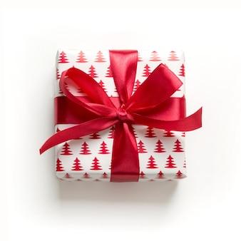Prezent na boże narodzenie z czerwoną kokardą na białym tle. boże narodzenie. szczęśliwy. nowy rok. płaski układ.