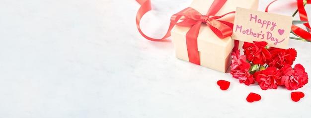 Prezent na dzień matki, czerwony bukiet goździków z zapakowanym prezentem z papieru pakowego związany wstążką na białym tle na marmurowym białym stole, z bliska.