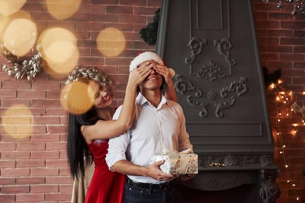 Prezent na nowy rok. brunetka dziewczyna zamknij oczy swojego mężczyzny w santa hat i zrób mu świąteczny prezent.