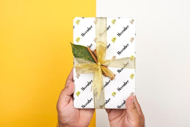Prezent na święto dziękczynienia. jasny prezent przewiązany wstążką i cynamonem. listopadowe pudełko na jasne