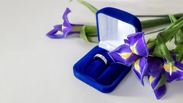 Prezent na walentynki - bukiet niebieskich irysowych kwiatów i pierścionek zaręczynowy w niebieskim aksamitnym pudełku