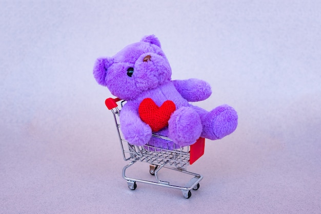 Prezent na walentynki. liliowy miś, jasna pluszowa zabawka z czerwonym sercem w wózku w supermarkecie. retro romantyczny styl.