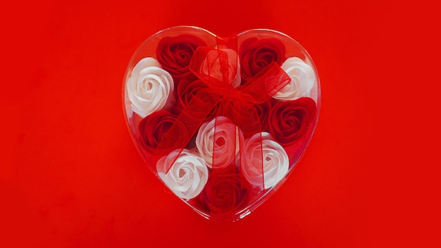 Prezent na walentynki na czerwono. dużo czerwono-białych róż w opakowaniu w kształcie serca, przewiązane czerwoną wstążką. pojęcie miłości