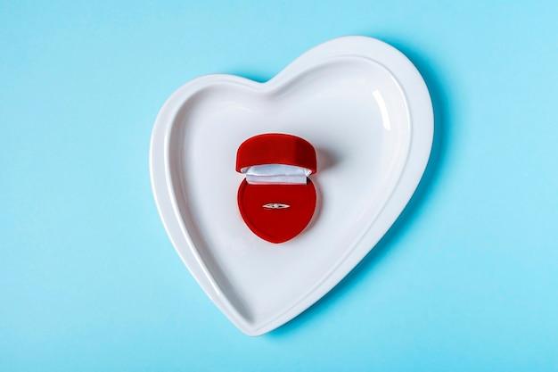Prezent na walentynki. pudełko na biżuterię ze złotym pierścionkiem z brylantem na talerzu w kształcie serca wśród czerwonych serc. propozycja małżeństwa, koncepcja zaangażowania. skopiuj miejsce na tekst