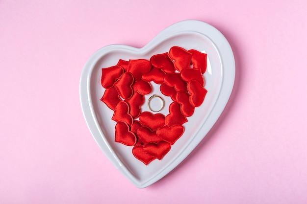Prezent na walentynki. złoty pierścionek z brylantem na talerzu w kształcie serca wśród czerwonych serc na różowej ścianie. propozycja małżeństwa, koncepcja zaangażowania. skopiuj miejsce na tekst,