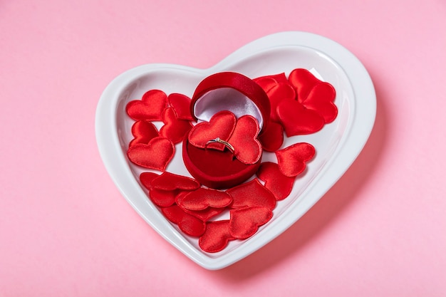 Prezent na walentynki. złoty pierścionek z brylantem w pudełku z biżuterią na talerzu w kształcie serca wśród czerwonych serc na różowej ścianie. propozycja małżeństwa, koncepcja zaangażowania. skopiuj miejsce na tekst.