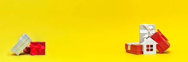 Prezent nieruchomości, prezent do domu. biały domek w pudełku prezentowym na żółtym tle. pocztówka do druku, baner z miejscem na tekst.