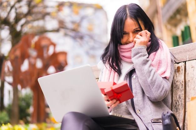 Prezent niespodzianka, portret bardzo podekscytowanej dziewczyny otwierającej prezent dla chłopaka podczas rozmowy wideo z komputerem, oddzielony odległością