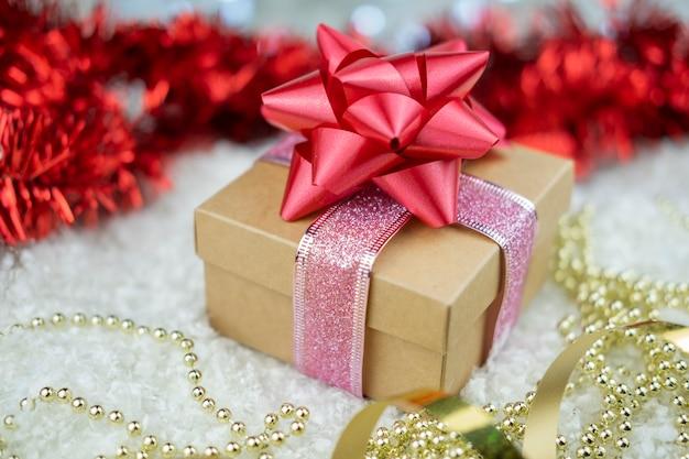 Prezent niespodzianka z czerwoną kokardką na śniegu lub noworoczne ferie zimowe i walentynki ze złotą serpentyną