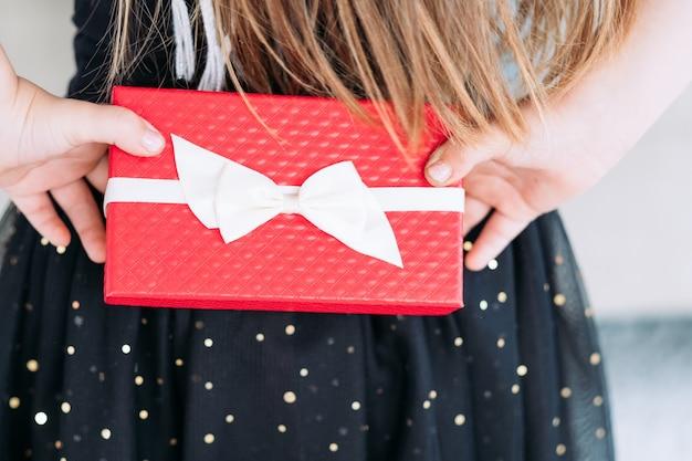 Prezent niespodzianka zapakowana w czerwone pudełko upominkowe z kokardką.