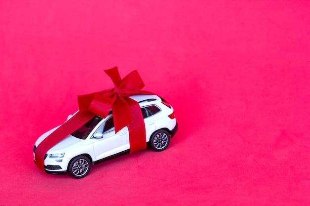 Prezent nowego samochodu z czerwoną kokardą na czerwono
