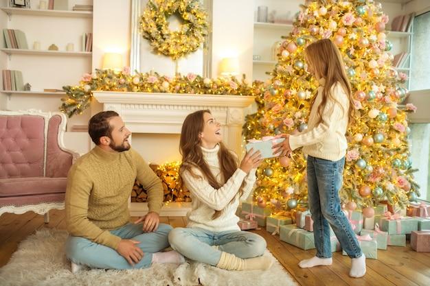 Prezent noworoczny. ładna dziewczyna, dając rodzicom prezent na nowy rok