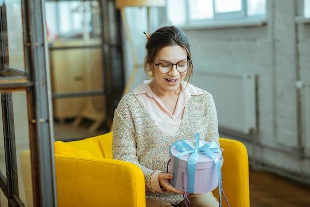 Prezent od męża. kobieta w ciąży zaskoczona po otrzymaniu prezentu od męża