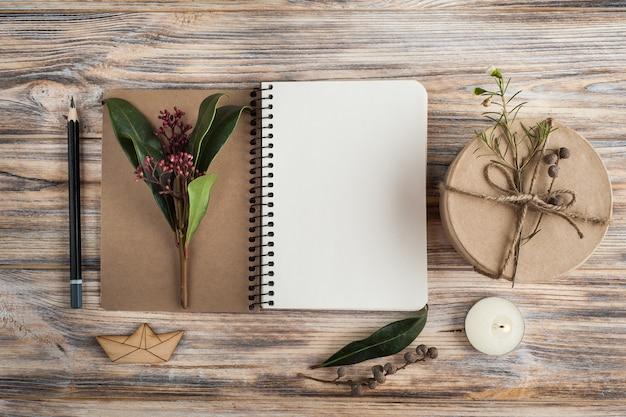 Prezent, otwarty notatnik i dekoracje kwiatowe