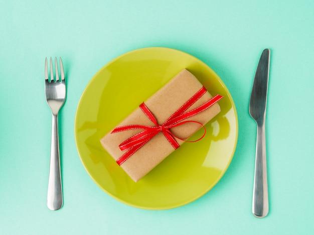 Prezent, paczka kraft brązowy papier z czerwoną wstążką na żółty talerz, nóż, widelec. walentynki