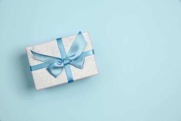 Prezent, pudełko na prezent. monochromatyczna stylowa i modna kompozycja w niebieskim kolorze na tle. widok z góry, układ płaski. czyste piękno zwykłych rzeczy wokół. miejsce na reklamę. wakacje, uroczystości.