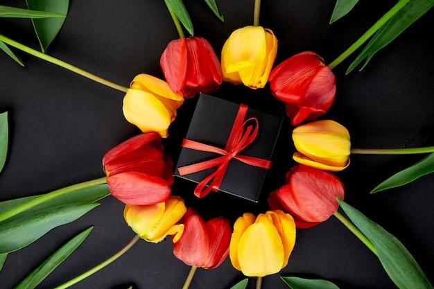 Prezent, pudełko z czerwonym i żółtym tulipanem wokół