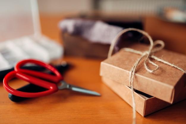 Prezent robótki ręczne i nożyczki na drewnianym stole. narzędzia rękodzieła. ręcznie robione akcesoria